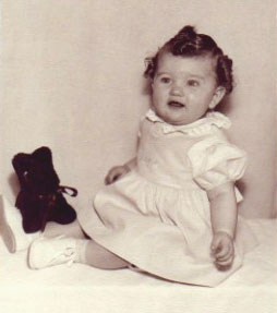 Gloria as a baby with her favorite stuffed dog toy.